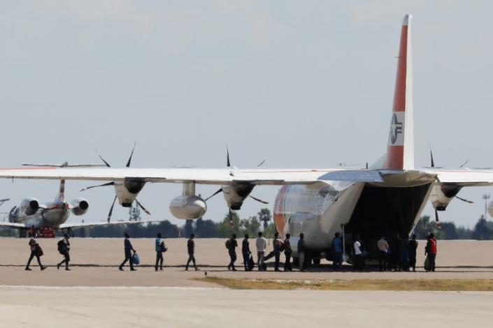 Migrants board a U.S. Coast Guard airplane at the Del Rio International Airport as U.S. authorities accelerate removal of migrants at border with Mexico, in Del Rio