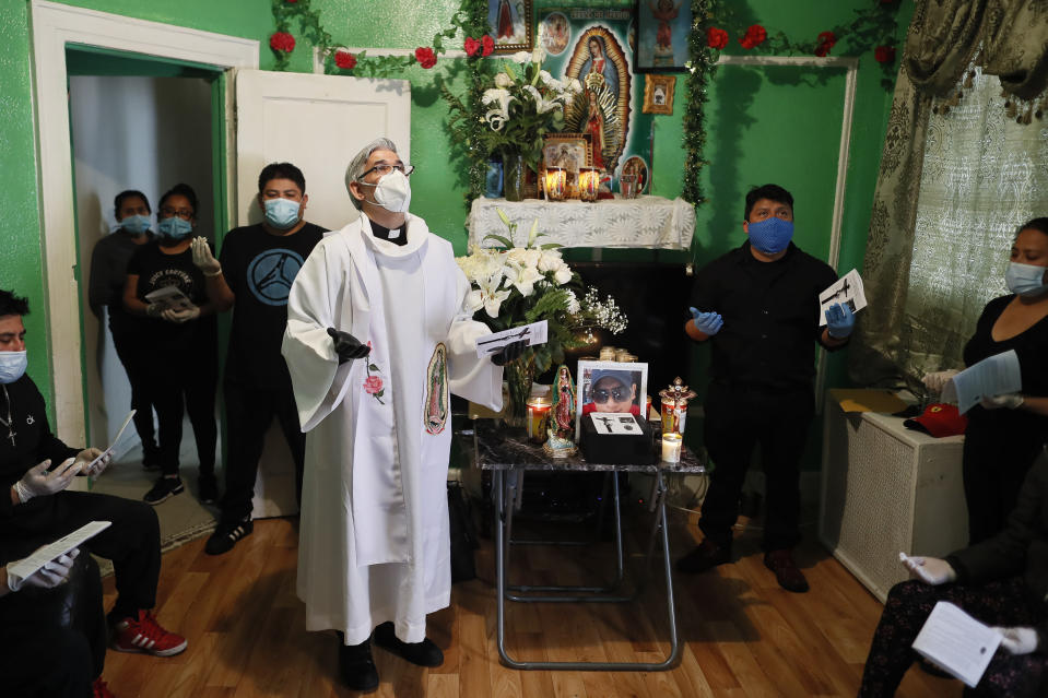 FILE - In this Saturday, May 9, 2020 file photo, the Rev. Fabian Arias performs an in-home service beside the remains of Raul Luis Lopez who died from COVID-19 the previous month, in the Corona neighborhood of the Queens borough of New York. (AP Photo/John Minchillo)