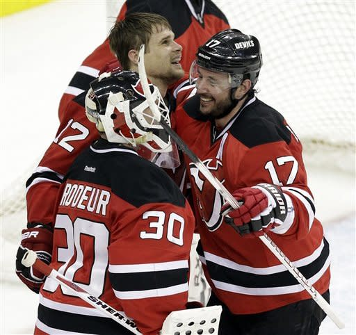 New Jersey Devils' Alexei Ponikarovsky, top, of Ukraine, celebrates his game-winning goal against the Philadelphia Flyers with teammates Ilya Kovalchuk (17), of Russia, and Martin Brodeur (30) in a 4-3 overtime victory in Game 3 of a second-round NHL hockey Stanley Cup playoff series, Thursday, May 3, 2012 in Newark, N.J. The Devils took a 2-1 lead in the series. (AP Photo/Julio Cortez)