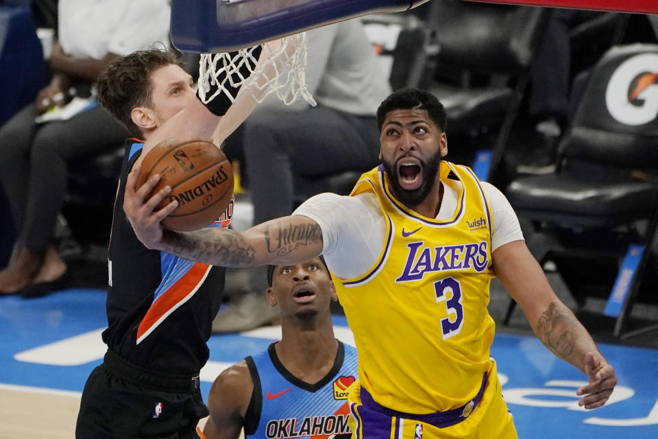 Los Angeles Lakers forward Anthony Davis (3) goes to the basket in front of Oklahoma City Thunder center Mike Muscala, left, and guard Shai Gilgeous-Alexander during the second half of an NBA basketball game Wednesday, Jan. 13, 2021, in Oklahoma City. (AP Photo/Sue Ogrocki)