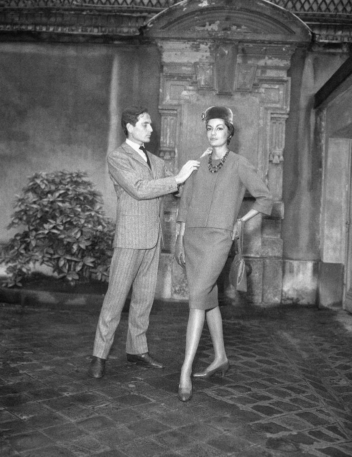 FILE - In this Sept.13, 1960 file photo, Parisian designer Pierre Cardin, with one of his models, shows the new uniform he has created for the hostesses of French television in Paris. France's Academy of Fine Arts says famed fashion designer Pierre Cardin has died at 98 (AP Photo/Pierre Godot, File)