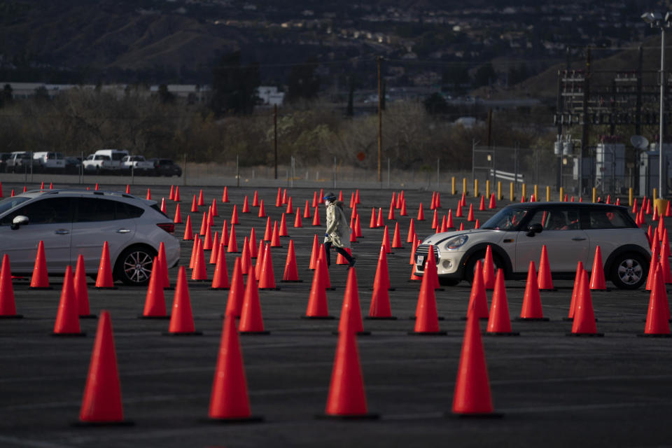 FILE - In this Jan. 22, 2021 file photo medical staff members walk between traffic cones at a mass COVID-19 vaccination site set up in the parking lot of Six Flags Magic Mountain in Valencia, Calif. Five weeks into its vaccination program, California still doesn't have nearly the supply to meet demand and there's growing angst among residents over the difficulty to even get in line for a shot. Social media is awash with people seeking or giving tips on how to maneuver through the system. (AP Photo/Jae C. Hong,File)