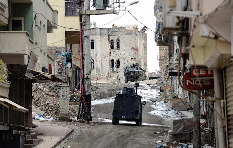Military vehicles in a deserted street of Silvan, Turkey during a curfew following clashes between Turkish forces and Kurdish militants on November 10, 2015 (AFP Photo/Ilyas Akengin)