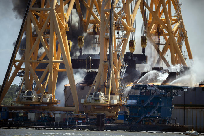 Firefighters working from the towering crane being used to dismantle the ship, hose down a fire in the overturned cargo ship Golden Ray, Friday, May 14, 2021, Brunswick, Ga. The Golden Ray had roughly 4,200 vehicles in its cargo decks when it capsized off St. Simons Island on Sept. 8, 2019. (AP Photo/Stephen B. Morton)