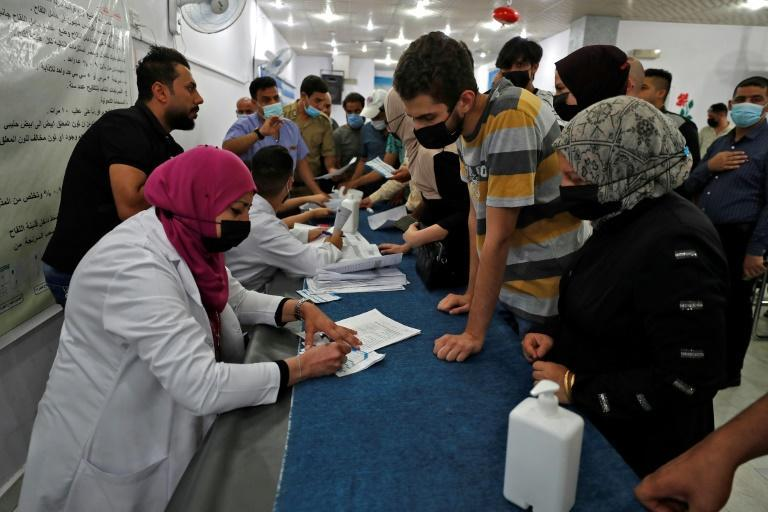 Iraqis register to get vaccinated against the coronavirus at an inoculation centre in Baghdad on July 27, 2021