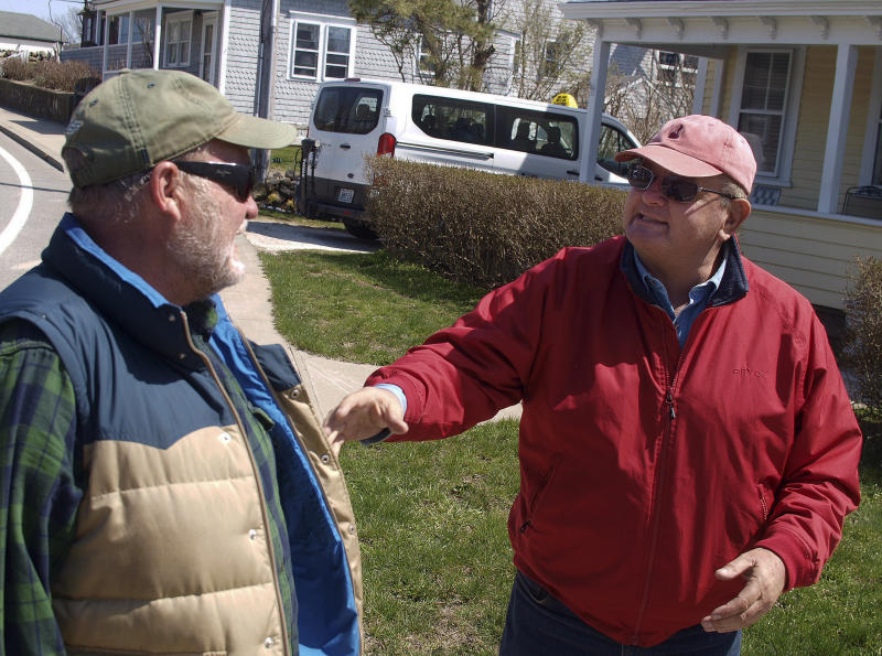 In this Tuesday, April 11, 2017 photo, Champlin Starr, left, talks with Leslie Slate in New Shoreham, R.I. The two men are among several dozen taxi drivers on Block Island. The community has had its own taxi rules since 1929. The wait to get a taxi license is about 15 years. (AP Photo/Matt O'Brien)