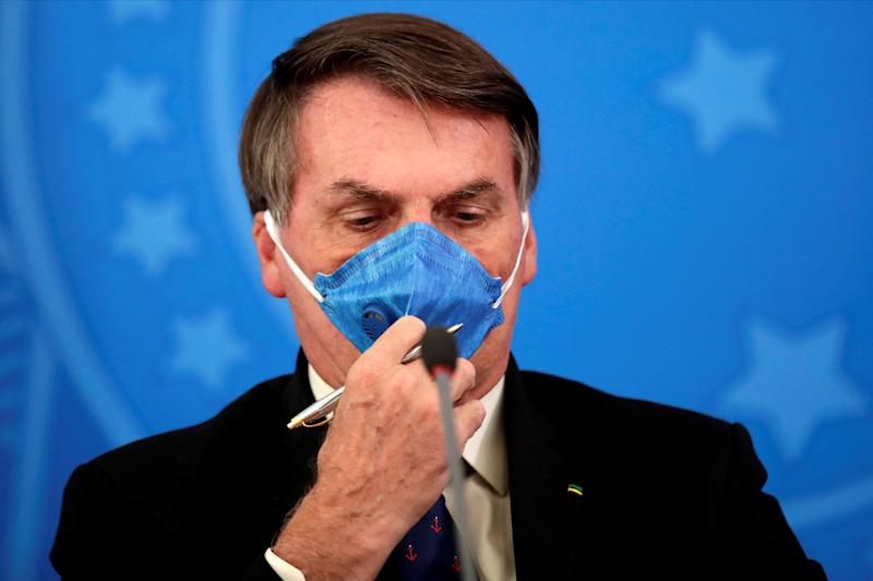 Brazil's President Jair Bolsonaro adjusts his protective face mask at a press statement during the coronavirus disease (COVID-19) outbreak in Brasilia, Brazil, March 20, 2020. Picture taken March 20, 2020. REUTERS/Ueslei Marcelino