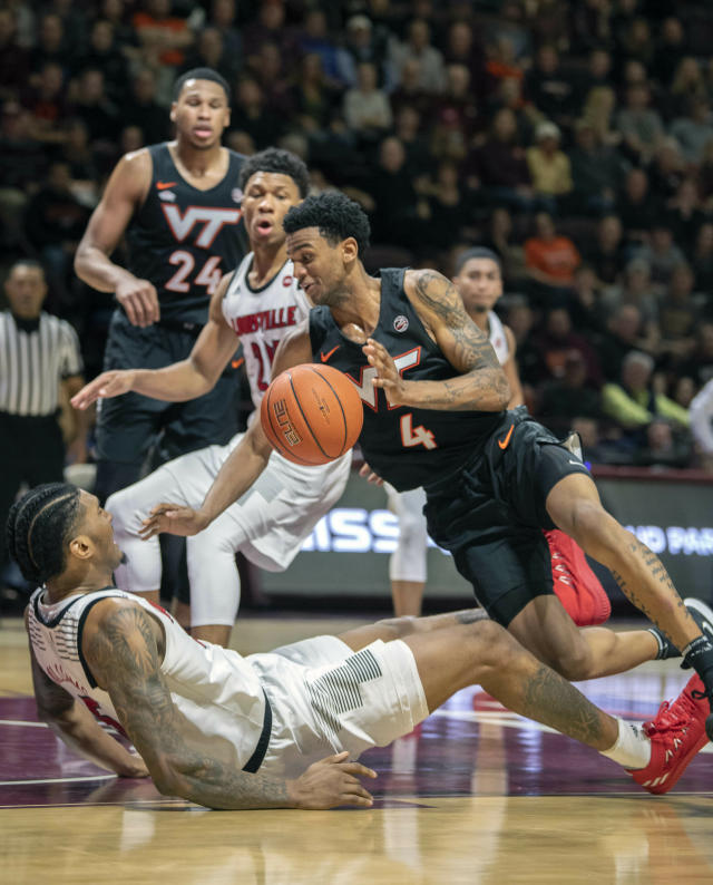 Louisville center Malik Williams, bottom, tries to draw a foul against Virginia Tech Hokies guard Nickeil Alexander-Walker (4) during the second half of an NCAA college basketball game Monday, Feb. 4, 2019, in Blacksburg, Va. (AP Photo/Don Petersen)