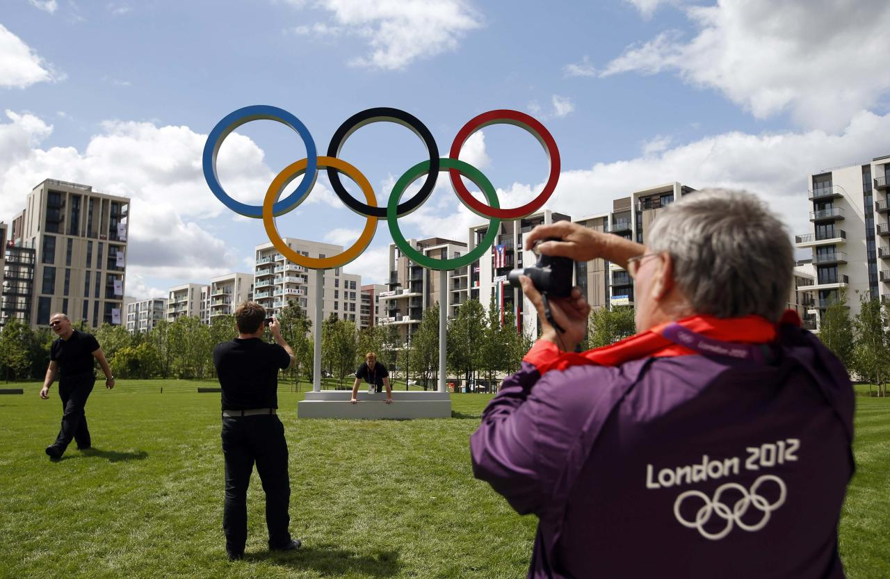 """A volunteer takes a photograph of the Olympic rings at the Athletes' Village at the Olympic Park in London in this July 19, 2012 file photo. Sleep deprived, rain-soaked and unpaid, London's army of  Olympic volunteers - officially known as """"games makers"""" - are surprisingly upbeat, and have won admiration for their work shepherding thousands of fans around sports venues.   REUTERS/Jae C. Hong/Pool/Files (BRITAIN - Tags: SPORT OLYMPICS)"""