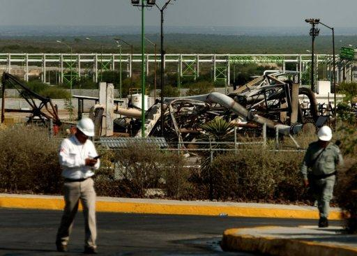 <p>PEMEX workers walk by the place where a fire in the gas plant killed at least twenty-six people in Reynosa, Mexico. The death toll from the fire rose to 29 while three workers remained missing Wednesday as witnesses recounted the terrifying blast and the inferno's intense heat.</p>