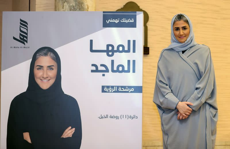 Al-Maha Al-Majid, a candidate in Qatar's Shura Council election, poses for a photo next to an election poster in Doha