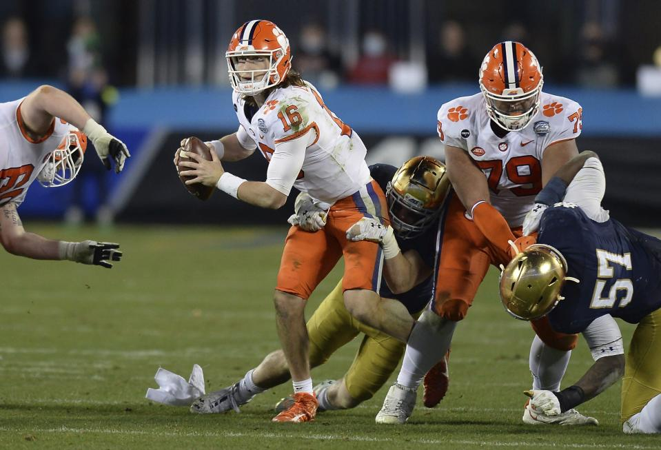 Clemson quarterback Trevor Lawrence (16) continues to look for a receiver as a Notre Dame defender wraps him up during the Atlantic Coast Conference championship NCAA college football game, Saturday, Dec. 19, 2020, in Charlotte, N.C. (Jeff Siner/The News & Observer via AP)