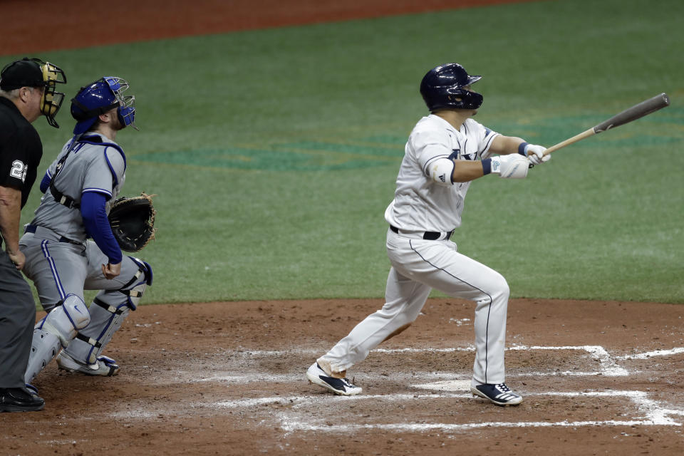 Tampa Bay Rays' Yoshitomo Tsutsugo, of Japan, right, watches his two-run home run off Toronto Blue Jays starting pitcher Hyun-Jin Ryu during the fifth inning of a baseball game Friday, July 24, 2020, in St. Petersburg, Fla. Following the play are Blue Jays catcher Danny Jansen (9) and home plate umpire Joe West. (AP Photo/Chris O'Meara)