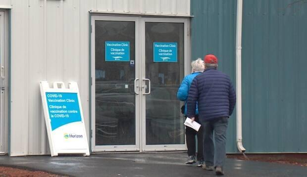 Residents arrive to get their AstraZeneca-Oxford vaccine at the Exhibition Park site in Saint John on Thursday. The clinic, for people 55 and over, was booked within two-and-a-half hours of being announced Tuesday, with 240 people signing up for shots. (Roger Cosman/CBC News - image credit)