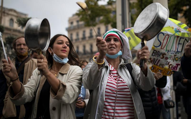 Restaurant owners bang pans at a demonstration against restaurant and bar closures in Marseille earlier this month - Daniel Cole/AP