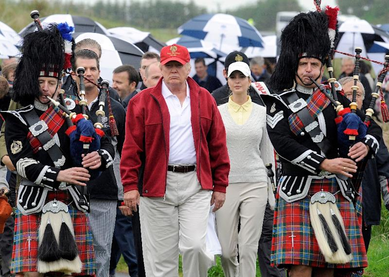 Donald Trump (C) is escorted by Scottish pipers as he officially opens his new multi-million pound Trump International Golf Links course in Aberdeenshire, Scotland on July 10, 2012 (AFP Photo/Andy Buchanan)