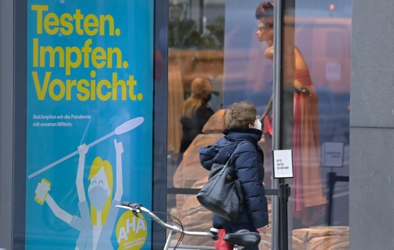 """A poster in Germany urges: """"Test. Vaccinate. Caution"""""""