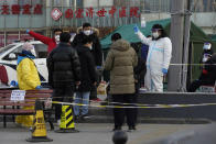 Residents line up for coronavirus tests at tents set up on the streets of Beijing on Sunday, Dec. 27, 2020. Beijing has urged residents not to leave the city during the Lunar New Year holiday in February, implementing new restrictions and mass testings after several coronavirus infections last week. (AP Photo/Ng Han Guan)
