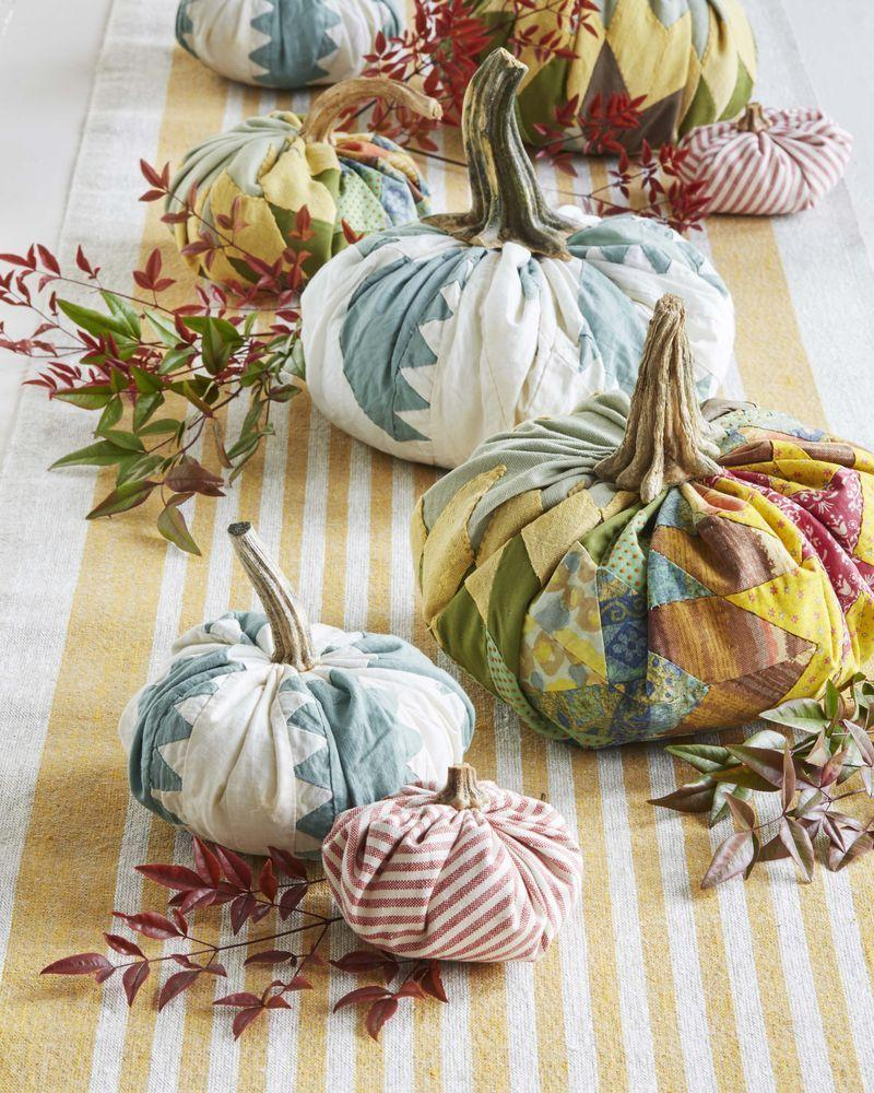 """<p>Craft your own personal pumpkin patch using old quilts and fabric scraps.</p><p><strong>To make:</strong> Start with a round piece of fabric and a ball of batting (about the size you want your finished pumpkin to be). Gather the fabric up around the batting and hot glue it together in the center. Collect dried stems, or purchase faux stems, and attach with hot glue for a realistic touch. Line the middle of a long farmhouse table with a runner, then pile on your creations and other seasonal greenery. These would be an adorable accent to a mantel or buffet as well.</p><p><a class=""""link rapid-noclick-resp"""" href=""""https://www.amazon.com/s?k=pumpkin+stems&i=handmade&ref=nb_sb_noss_2&tag=syn-yahoo-20&ascsubtag=%5Bartid%7C10050.g.2063%5Bsrc%7Cyahoo-us"""" rel=""""nofollow noopener"""" target=""""_blank"""" data-ylk=""""slk:SHOP FAUX PUMPKIN STEMS"""">SHOP FAUX PUMPKIN STEMS</a></p>"""