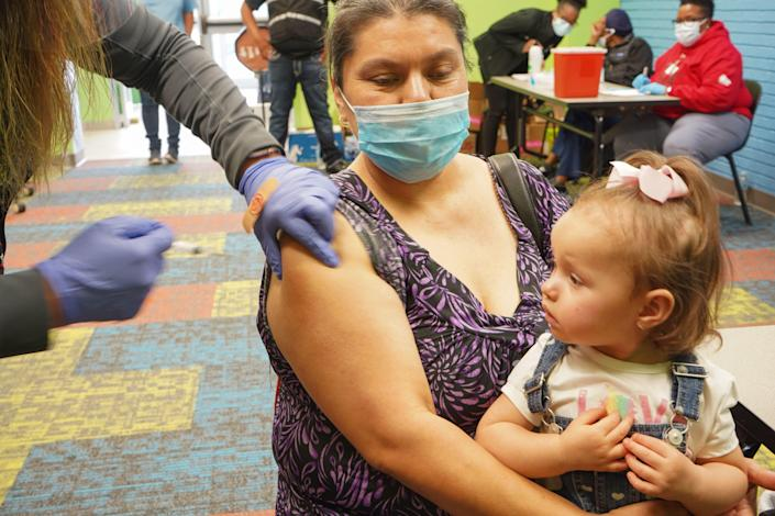 Healthcare vaccinated a woman with the Covid-19 vaccine on April 30, 2021, as the Pasadena Public Library hosted a mobile vaccine clinic established by Harris County Public Health in Pasadena, Texas.  / Credit: CECILE CLOCHERET / AFP via Getty Images