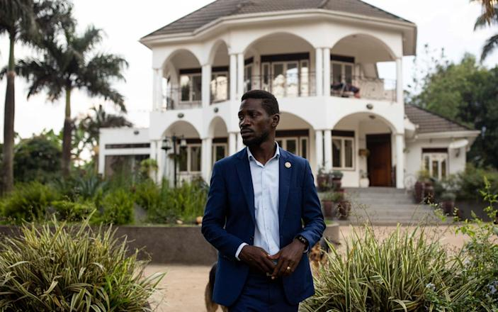 Bobi Wine stands outside his home as security forces surround his property on January 15 - Getty Images