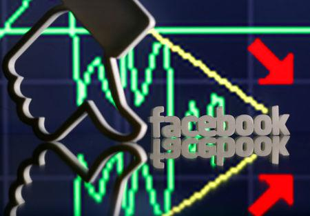 A 3D-printed Facebook logo and Like are seen in front of displayed stock graph