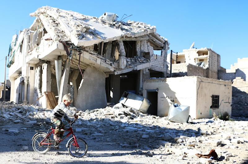 A boy rides his bike past a destroyed building in the northern Syrian city of Aleppo, on November 5, 2014 (AFP Photo/Baraa al-Halabi)