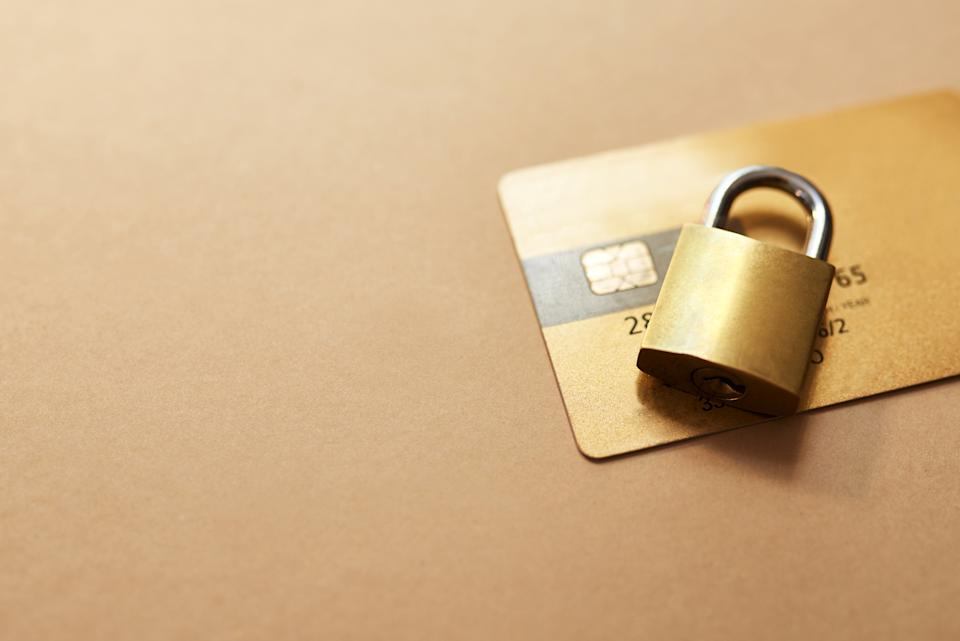 Studio shot of a credit card and lock against a brown background