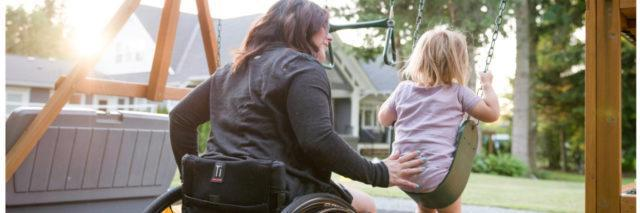 Woman in wheelchair pushing her child on a swing.