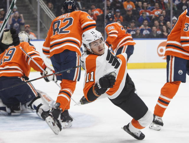 Philadelphia Flyers' Travis Konecny (11) is checked by Edmonton Oilers' Caleb Jones (82) during first-period NHL hockey game action in Edmonton, Alberta, Friday, Dec. 14, 2018. (Jason Franson/The Canadian Press via AP)