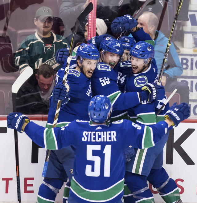 Vancouver Canucks' Michael Del Zotto, back from left to right, Tim Schaller, Tyler Motte, Jay Beagle and Troy Stecher (51) celebrate Motte's goal against the Minnesota Wild during the second period of an NHL hockey game, Tuesday, Dec. 4, 2018, in Vancouver, British Columbia. (Darryl Dyck/The Canadian Press via AP)