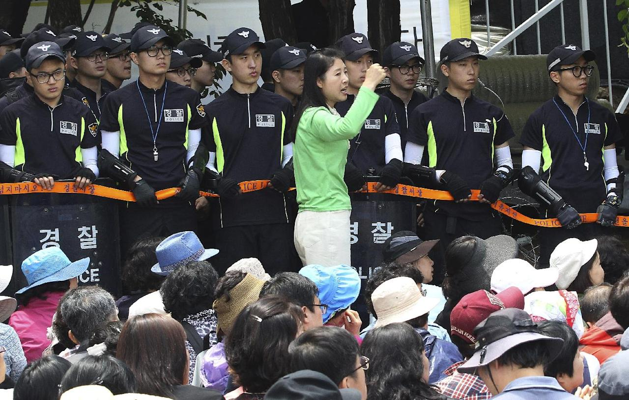 An Evangelical Baptist Church believer shouts slogans against the government as police officers stand guard in font of believers sitting by the main gate of the church in Anseong, South Korea, Wednesday, June 11, 2014. Thousands of South Korean police officers stormed a church compound Wednesday in their hunt for a fugitive billionaire businessman over April's ferry sinking that left more than 300 people dead or missing, officials said. (AP Photo/Ahn Youn-joon)