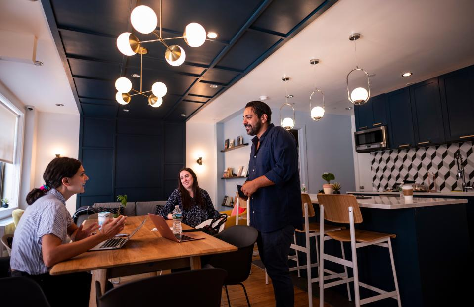 """Gil Hirak (R), head of US operations and community of Quarters speaks with colleagues in the community living area of Quarters Co-Living in the Lower East Side on July 24, 2019 in New York City. - Nandita Iyer landed in New York from Bombay without knowing anyone, but she didn't want to live alone in a """"sketchy studio."""" So instead she opted for a room in a """"coliving"""" unit. She lives with roommates in one of the 14 apartments in a small building run by the housing start-up Quarters in the trendy Lower East Side neighborhood. The best part of the arrangement, she said, are the common areas: a large kitchen with a big table and comfy couches, a terrace where she can work and a luxurious rooftop patio. """"I met people from such different backgrounds. And I became very good friends with them,"""" she said. (Photo by Johannes EISELE / AFP)        (Photo credit should read JOHANNES EISELE/AFP via Getty Images)"""