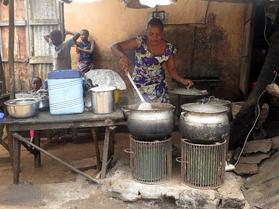 Philomene Ahouansou cooks beans and rice by the roadside using a solar-powered cooker in Porto-Novo, Benin (AFP Photo/Delphine Bousquet)