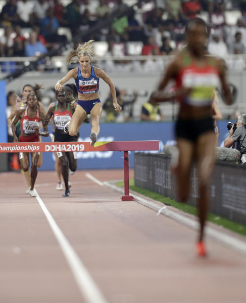 Emma Coburn, of the United States chases runaway leader Beatrice Chepkoech, of Kenya, the women's 3000 meter steeplechase final at the World Athletics Championships in Doha, Qatar, Monday, Sept. 30, 2019. (AP Photo/Petr David Josek)