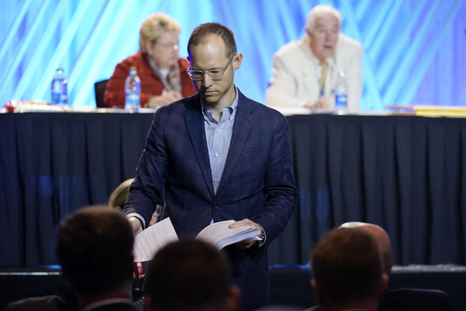 Dr. Jared Wellman, pastor at Tate Springs Baptist Church in Arlington, Texas, hands out copies of his motion during the executive committee plenary session at the denomination's annual meeting Monday, June 14, 2021, in Nashville, Tenn. Wellman's motion called for an independent committee to lead a probe of the denomination's handling of sex abuse cases. (AP Photo/Mark Humphrey)