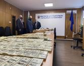 In this photo provided by the Bulgarian Prosecutor's office on Tuesday, March 16, 2021 counterfeit money displayed on table at Bulgarian Prosecutor's office as officials stand near, in Sofia. Bulgarian authorities say they have seized high-quality forged banknotes produced at a printing office in a university in the Bulgarian capital. In a joint operation with U.S. Secret Service, Bulgarian police detained two people and seized a printing machine and equipment for printing money, along with large amounts of counterfeit U.S. dollar and euro notes. (AP Photo/ Bulgarian Prosecutor's office)