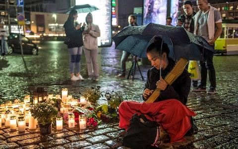 A girl plays a traditional Finnish instrument 'kantele' and singing a traditional lullaby at the site where one person was stabbed to death - Credit: EPA/MARKKU OJALA