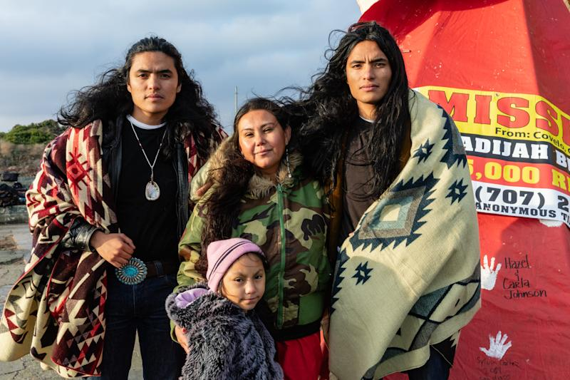 Brothers, models, and indigenous rights activists Haatepah and Nyamuull Clearbear with event organizer Morning Star Gali.
