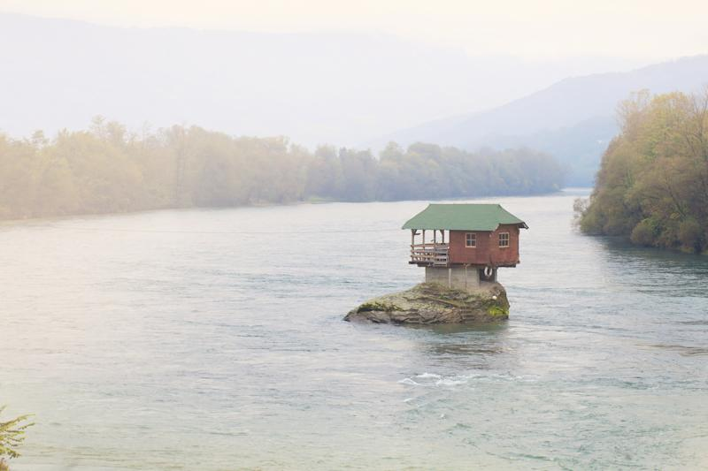 A lone house sitting on a rock surrounded by a river.