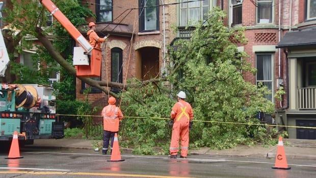Crews work to remove part of tree on Gerrard Street East near Ontario Street in Toronto on Tuesday. A severe thunderstorm pounded Toronto in the afternoon — leaving behind downed trees and wires, flooded roads and basements and some elevators stalled due to power outages. (CBC - image credit)