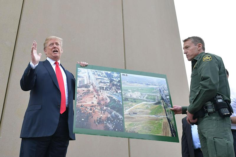 Mr Trump and Mr Scott with images of the border wall prototypes: Getty