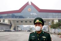 FILE PHOTO: A Vietnamese border guard officer wearing protective mask stands guard at Huu Nghi border gate connecting with China, in Lang Son province, Vietnam