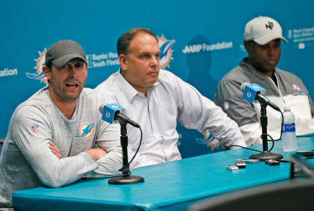 FILE - In this Jan. 3, 2018, file photo, Miami Dolphins head coach Adam Gase, left, answers a question during a news conference with Mike Tannenbaum, center, executive vice president of football operations, and Chris Grier, general manager, at the teams NFL football training camp in Davie, Fla. The tension between seeking an immediate draft dividend and investing for the long term is at the core of the Dolphins decision with the 11th overall pick. The choice may show how much power Gase wields, but even if the other leaders in the organization yield to his preference, its uncertain which quarterback will land in Miami. (AP Photo/Wilfredo Lee, File)