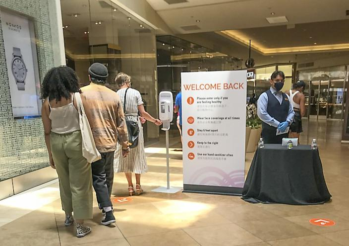 "A ""welcome back"" sign put up a month ago greets shoppers at South Coast Plaza on Monday. Most counties, including Los Angeles, will be forced to shutter malls, gyms, churches, hair salons and other businesses under a new order. <span class=""copyright"">(Allen J. Schaben / Los Angeles Times)</span>"