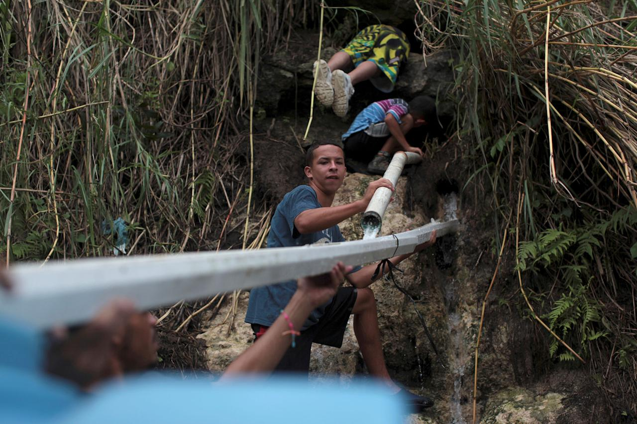 <p>People collect mountain spring water, after Hurricane Maria hit the island, in Corozal, Puerto Rico, Oct. 17, 2017. (Photo: Alvin Baez/Reuters) </p>