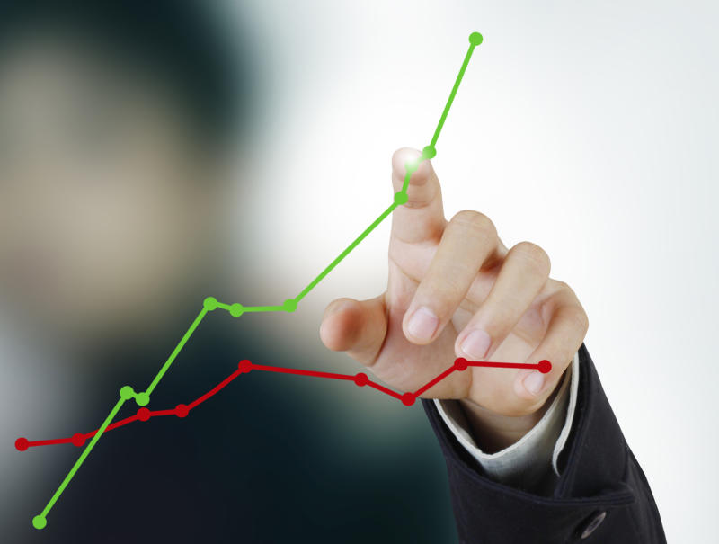 A person pointing to an upwardly sloping line chart that's above a flat line chart