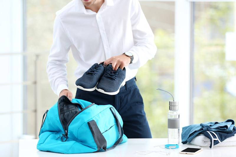 businessman packing sports stuff for training into bag in office