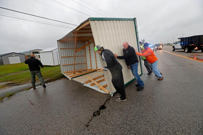 People move a wood and metal structure off a roadway after winds blew it off a sales lot in Florence, South Carolina.