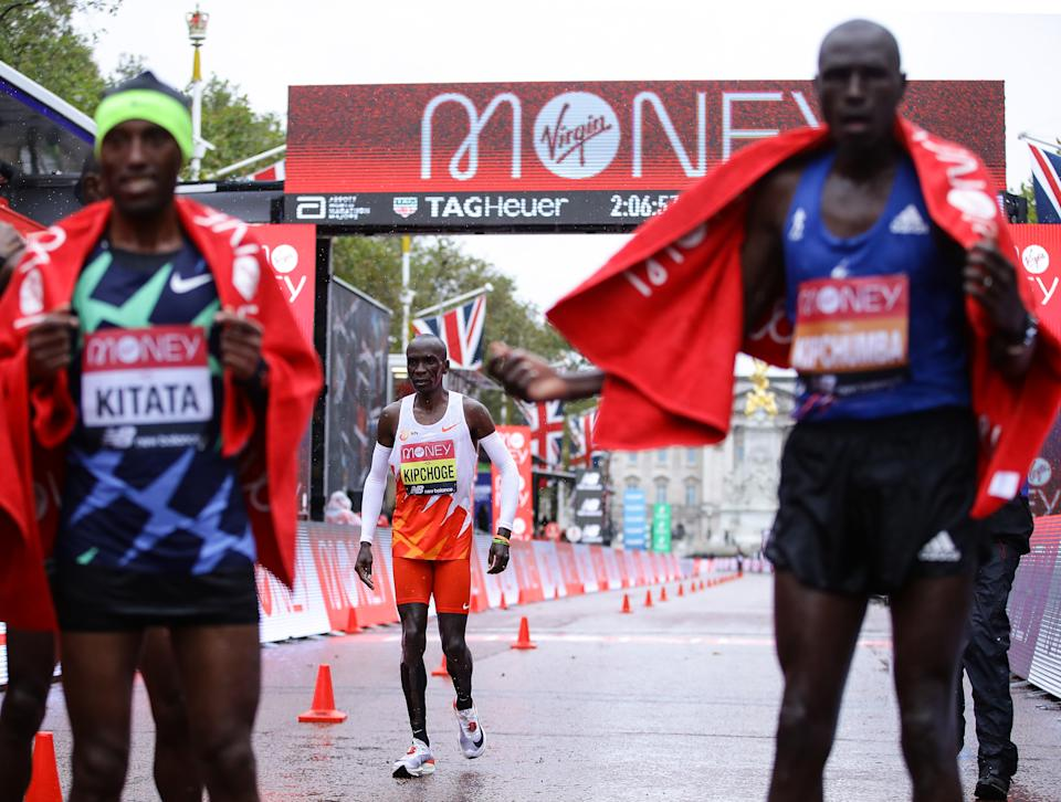 LONDON, ENGLAND - OCTOBER 04: Eliud Kipchoge of Kenya reacts as he crosses the line as first place Shura Kitata of Ethiopia and second place Vincent Kipchumba of Kenya celebrate following the Elite Men's race during the 2020 Virgin Money London Marathon around St. James's Park on October 04, 2020 in London, England. The 40th Race will take place on a closed-loop circuit around St. James's Park in central London. (Photo by Richard Heathcote/Getty Images)